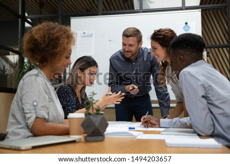 Asian female employee tell project idea talk to happy multiethnic team work group brainstorming discussing planning corporate strategy doing paperwork analyzing financial data at office meeting table