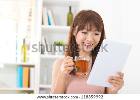 Asian female enjoying cup of tea looking at digital tablet computer inside house