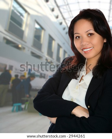 Asian female event organiser with exhibition in background.