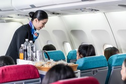 Asian female flight attendant serving food and drink to passengers on airplane. The cabin crew pushing the cart on aisle to serve the customer. Airline service job and occupation concept.
