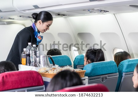 Asian female flight attendant serving food and drink to passengers on airplane. The cabin crew pushing the cart on aisle to serve the customer. Airline service job and occupation concept. Stockfoto ©