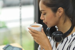 Asian female freelancer sipping hot tea, relaxed after a long work at cafe