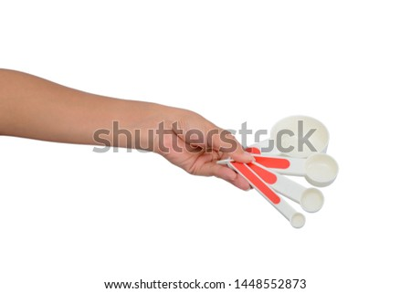 Asian female hands are holding plastic Measuring spoon isolated on white isolated on white background with clipping path #1448552873