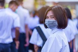 Asian female high school student in white uniform on the semester start wearing masks during the Coronavirus 2019 (Covid-19) epidemic.