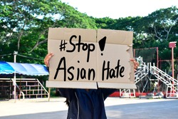 Asian female holds a paper sign with English words '#Stop Asian Hate', concept for calling the international community to stop the hatred of the Asian people that has caused spreading of the covid-19.