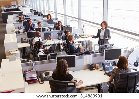 Asian female manager addressing workers in open plan office