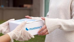 Asian female patient receive medication package box free first aid from pharmacy hospital delivery service at home wear glove in telehealth, telemedicine healthcare insurance online concept.