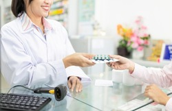 asian female pharmacist explain about how to use drug, she holding drug strip pack with her hand and talk with customer in drugstore, pharmacist send drug to patient