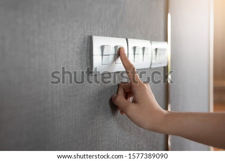 Asian female right hand is turning on or off on grey light switch over gray textile texture wall at the house or hotel. Copy space. Foto d'archivio ©