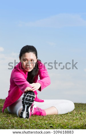 Asian female runner stretching before going running.