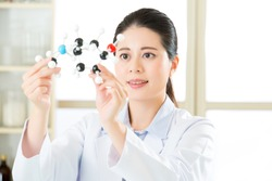 asian female scientist Examining the building blocks of life with molecular model in laboratory
