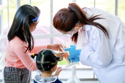 Asian female scientist teacher wears safety goggles white lab coat rubber gloves teaching little curious preschool girls observing studying on human anatomy from hand skeleton model in laboratory.