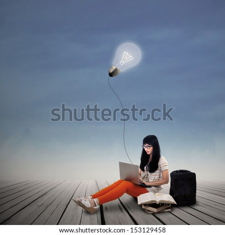 Asian female student is working on laptop under lit bulb outdoor