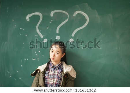 asian female student with lots of question marks in front of blackboard