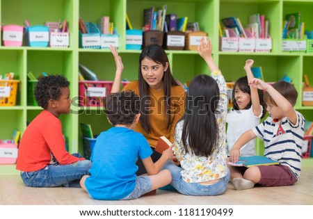 Asian female teacher teaching and asking mixed race kids hand up to answer in classroom,Kindergarten pre school concept - Shutterstock ID 1181190499
