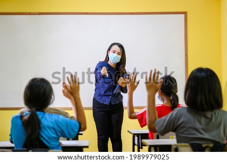 Asian female teacher Wearing a mask to prevent coronavirus (COVID 19) teaching elementary school students in a rural school and students raise their hands to answer the teacher's questions. Stock fotó ©