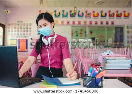 Asian female teacher wearing mask, doctor is teaching kindergarten students online Teachers and students watch lessons on a computer screen using online video conferencing systems to teach students.