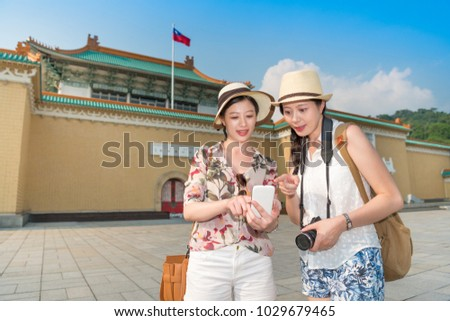 Asian female traveler sharing information pictures maps with each other by using a smartphone. They both carrying a travel back.