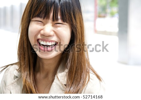Asian female with her cheerful smile, outside modern building.