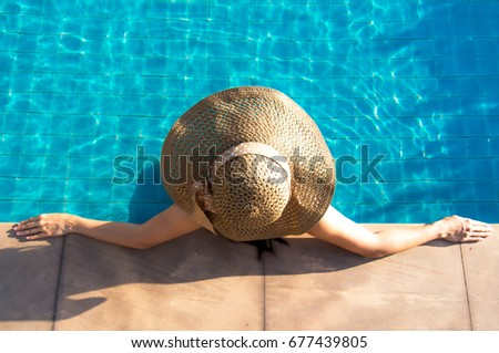Asian female Women lifestyle relaxing and rest near luxury swimming pool sunbath, summer day at the beach resort in the vacation hotel. Summer Concept.
