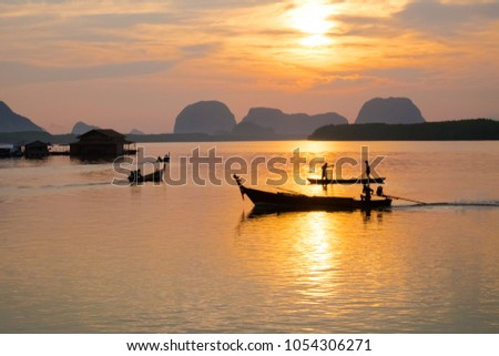 Asian fisherman  boat throws a net catching freshwater fish in a natural river in the morning