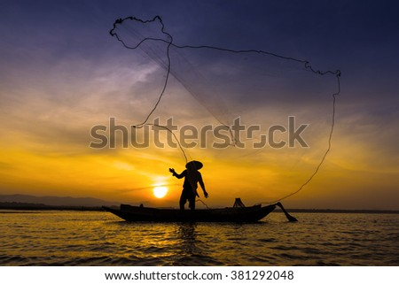 Asian fisherman on wooden boat casting a net for catching freshwater fish in nature river in the early morning before sunrise #381292048