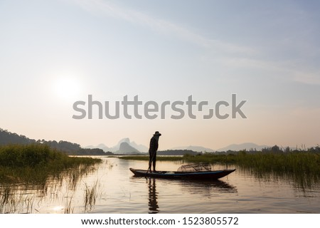 Asian Fishermen paddling wooden boat prepare fishing on the lake in the evening, sunset. Concept Fisherman's Lifestyle in countryside. Lopburi, Thailand, Asia #1523805572