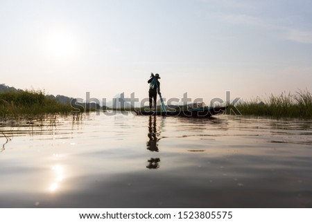 Asian fishermen prepare fishing net during sunset on boats at the lake.  Concept Fisherman's Lifestyle in countryside. Lopburi, Thailand, Asia #1523805575
