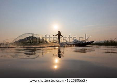 Asian fishermen throwing fishing net during sunset on wooden boat at the lake. Concept Fisherman's Lifestyle in countryside. Lopburi, Thailand, Asia #1523805527