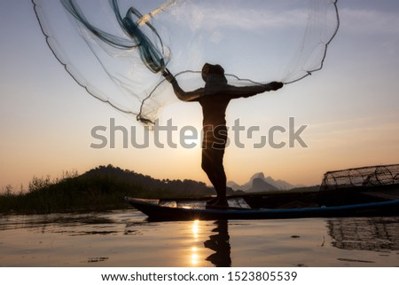 Asian fishermen throwing fishing net during sunset on wooden boat at the lake. Concept Fisherman's Lifestyle in countryside. Lopburi, Thailand, Asia #1523805539