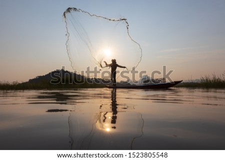 Asian fishermen throwing fishing net during sunset on wooden boat at the lake. Concept Fisherman's Lifestyle in countryside. Lopburi, Thailand, Asia #1523805548