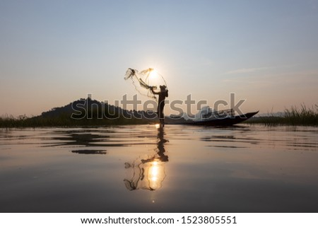 Asian fishermen throwing fishing net during sunset on wooden boat at the lake. Concept Fisherman's Lifestyle in countryside. Lopburi, Thailand, Asia #1523805551