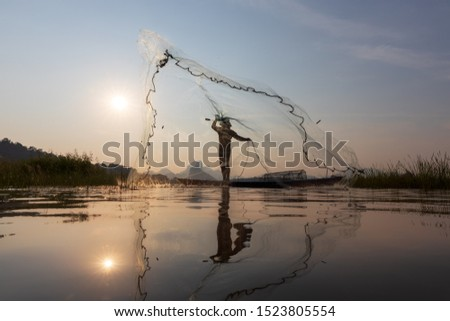 Asian fishermen throwing fishing net during sunset on wooden boat at the lake. Concept Fisherman's Lifestyle in countryside. Lopburi, Thailand, Asia #1523805554