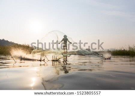 Asian fishermen throwing fishing net during sunset on wooden boat at the lake. Concept Fisherman's Lifestyle in countryside. Lopburi, Thailand, Asia #1523805557