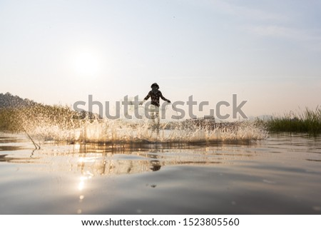 Asian fishermen throwing fishing net during sunset on wooden boat at the lake. Concept Fisherman's Lifestyle in countryside. Lopburi, Thailand, Asia #1523805560