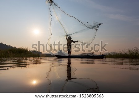Asian fishermen throwing fishing net during sunset on wooden boat at the lake. Concept Fisherman's Lifestyle in countryside. Lopburi, Thailand, Asia #1523805563