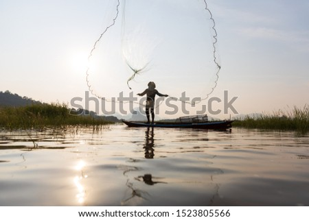 Asian fishermen throwing fishing net during sunset on wooden boat at the lake. Concept Fisherman's Lifestyle in countryside. Lopburi, Thailand, Asia #1523805566