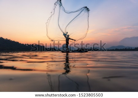 Asian fishermen throwing fishing net during twilight on wooden boat at the lake. Concept Fisherman's Lifestyle in countryside. Lopburi, Thailand, Asia #1523805503
