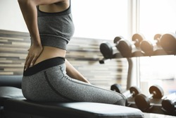 Asian Fitness woman having lower back pain after lifting too heavy dumbbells while workout. Female Athlete in grey sportswear suffering and injury from exercise at the gym. Muscle sprains.