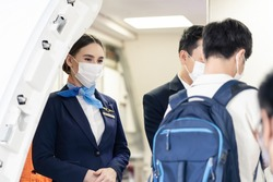Asian flight attendants wearing face mask greeting passengers walking and coming on board in airplane during the Covid pandemic to prevent coronavirus infection. Healthcare in transportation concept.