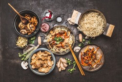 Asian food cooking. Wok with noodles chicken stir fry and vegetables ingredients with spices ,sauces and chopsticks on dark rustic background, top view