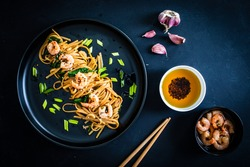Asian food - noodles with prawns in soy sauce with spinach on black table