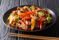 Asian food: teriyaki beef with red and yellow bell peppers, broccoli and sesame seeds close-up on a plate on a black table. horizontal