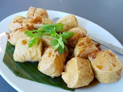 Asian food Tofu simmered in soy sauce with deep fried garlic and coriander. Traditional fried tofu on banana leaf.Asian food concept,soft focus,Select focus