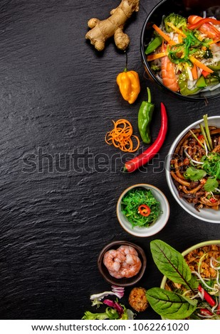 Asian food variation with many kinds of meals. Kari rice, noodles and vegetable. Top view, served on black stone.