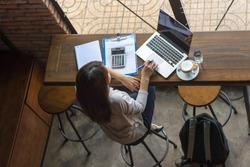 Asian freelancer working on laptop at cafe