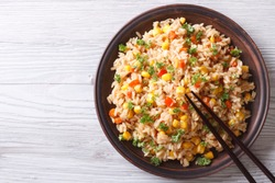 Asian fried rice with eggs, corn and parsley close-up on a plate, horizontal view from above