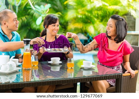 Asian friends having coffee on the porch in front of a home, in the background a tropical garden