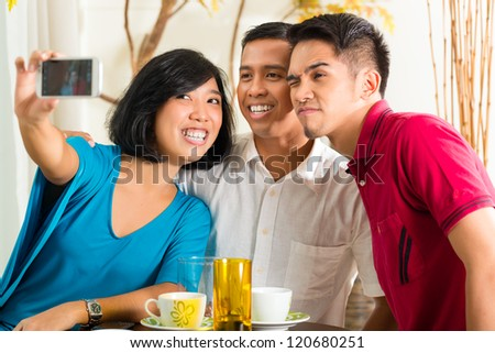 Asian friends, two men and a woman, having fun taking pictures with mobile phone - stock photo
