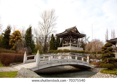 Asian Garden.Temple landscape or landmark with asian style. Japanese Garden with a lot of bonsai, a river and also a bridge. Typical for a chinese garden are the stones and plants.